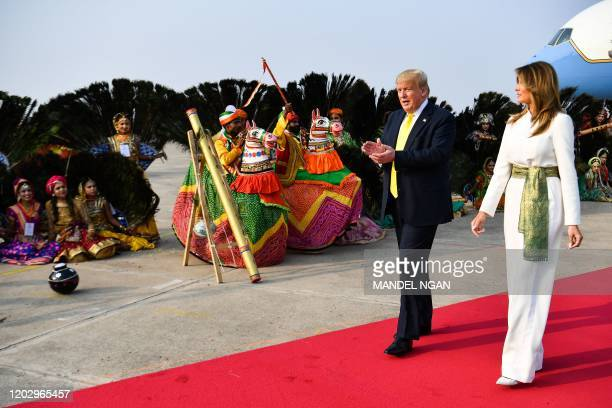 US President Donald Trump and First Lady Melania Trump are greeted by performers wearing traditional costumes as they arrive at Agra Air Base in Agra...