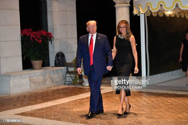 US President Donald Trump and First Lady Melania Trump arrive for a Christmas Eve dinner with his family at MarALago in Palm Beach Florida on...