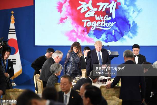 US President Donald Trump and First Lady Melania Trump arrive for a state dinner with South Korea's President Moon JaeIn at the presidential Blue...