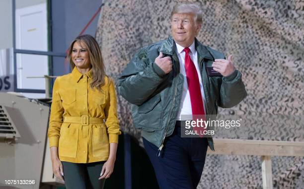 President Donald Trump and First Lady Melania Trump arrive to speak to members of the US military during an unannounced trip to Al Asad Air Base in...