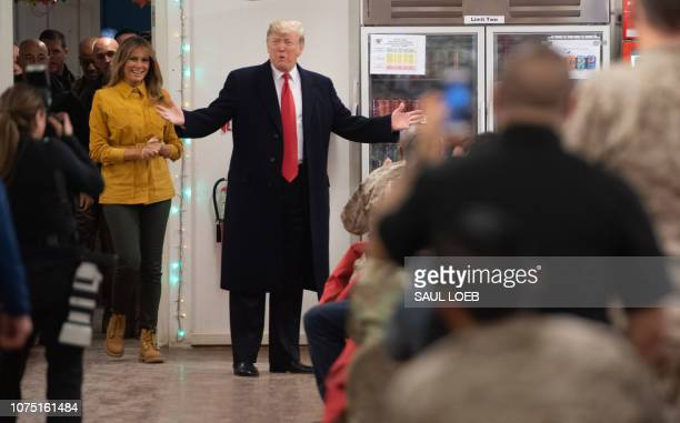 US President Donald Trump and First Lady Melania Trump arrive to visit members of the US military during an unannounced trip to Al Asad Air Base in...