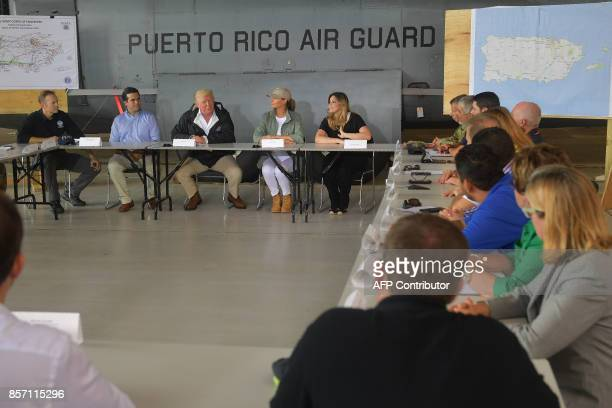 US President Donald Trump and First Lady Melania Trump attend a meeting with Governor Ricardo Rossello and other officials after stepping off Air...