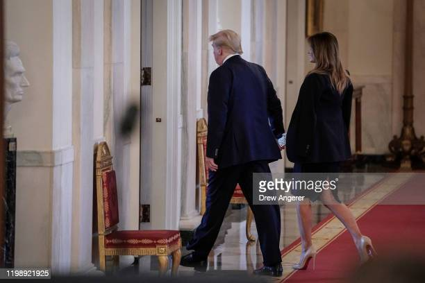 US President Donald Trump and First Lady Melania Trump exit after speaking in the East Room of the White House one day after the US Senate acquitted...