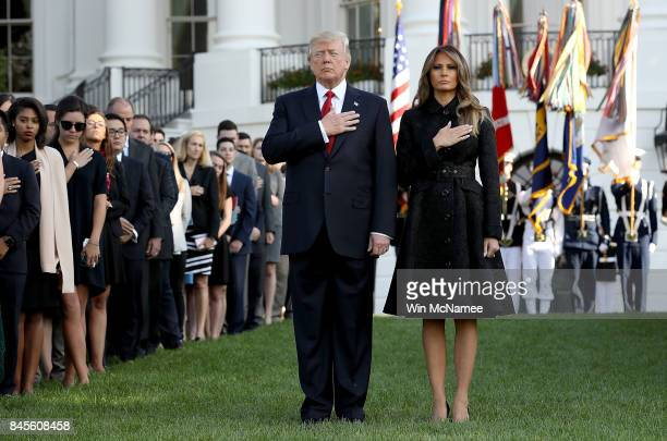 S President Donald Trump and first lady Melania Trump flanked by White House staff place their hands over their hearts on the South Lawn of the White...