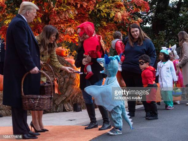 US President Donald Trump and First Lady Melania Trump give out candy to children at a Halloween celebration at the White House in Washington DC on...