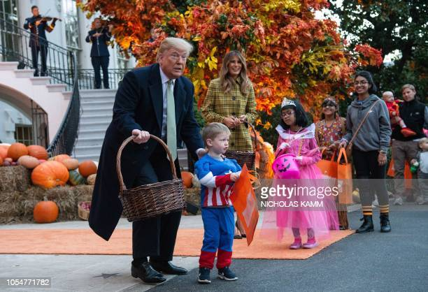 President Donald Trump and First Lady Melania Trump give out candy to children at a Halloween celebration at the White House in Washington DC on...