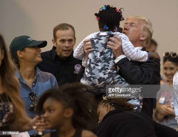 President Donald Trump and First Lady Melania Trump greet a young Hurricane Harvey victim at NRG Center in Houston on September 2, 2017. / AFP PHOTO...