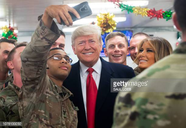 President Donald Trump and First Lady Melania Trump greet members of the US military during an unannounced trip to Al Asad Air Base in Iraq on...