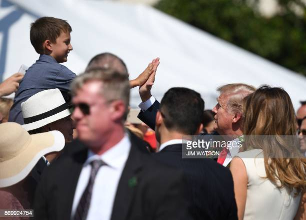 US President Donald Trump and First Lady Melania Trump greet wellwishers at Joint Base Pearl HarborHickam in Hawaii on November 3 2017 The Trumps are...
