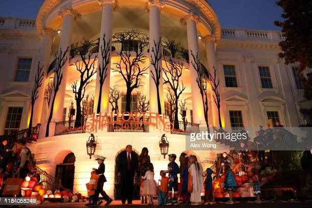 S President Donald Trump and first lady Melania Trump hand out candy to children as they trickortreat during a Halloween at the White House event at...