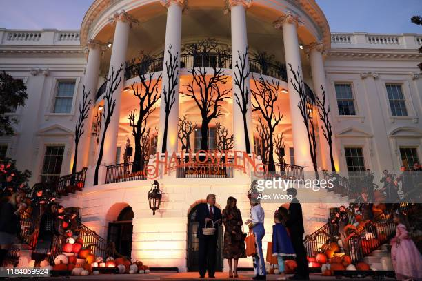 S President Donald Trump and first lady Melania Trump hand out candy to trickortreaters during a Halloween at the White House event at the South...