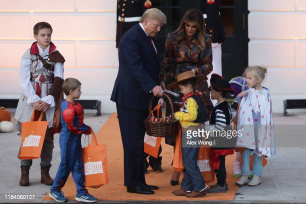 President Donald Trump and first lady Melania Trump hand out candy to children as they trick-or-treat during a Halloween at the White House event at...