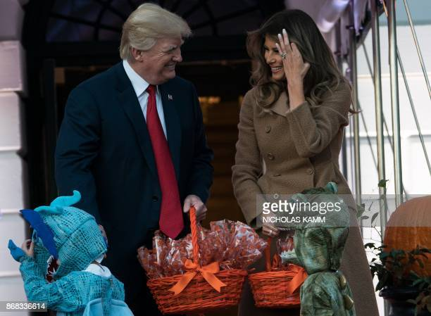 US President Donald Trump and First Lady Melania Trump hand out candy to children during a Halloween event at the White House in Washington DC on...