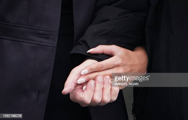 US President Donald Trump and First Lady Melania Trump hold hands as they make their way to board Marine One from the South Lawn of the White House...