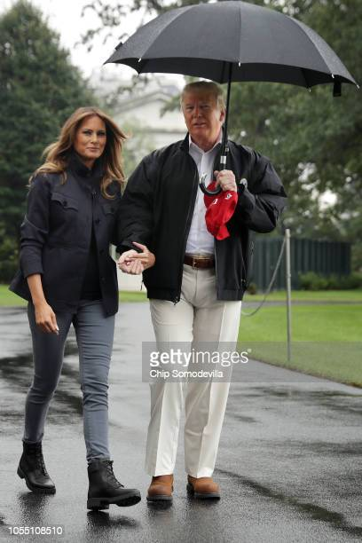 S President Donald Trump and first lady Melania Trump hold hands as they leave the White House October 15 2018 in Washington DC The Trumps are...