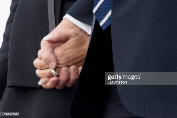 US President Donald Trump and First Lady Melania Trump hold hands as they walk off Air Force One arriving in West Palm Beach Florida on March 2 2018...