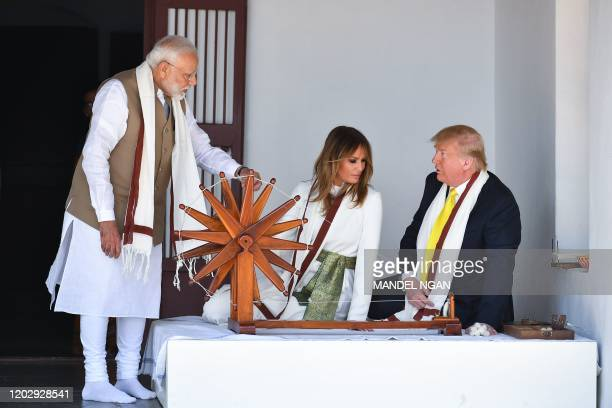 President Donald Trump and First Lady Melania Trump listen to India's Prime Minister Narendra Modi as they sit next to a charkha or spinning wheel...