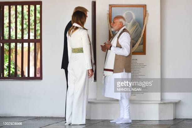 US President Donald Trump and First Lady Melania Trump listen to India's Prime Minister Narendra Modi as they visit the Gandhi Ashram in Ahmedabad on...