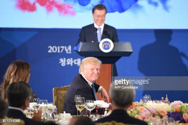 US President Donald Trump and First Lady Melania Trump listen to South Korea's President Moon JaeIn speak during a state dinner at the presidential...