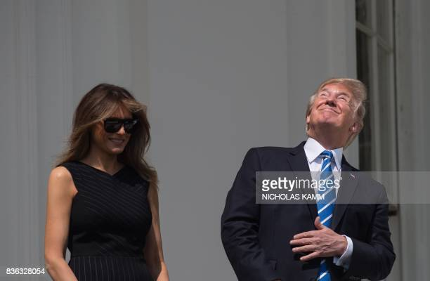 US President Donald Trump and First Lady Melania Trump look up at the partial solar eclipse from the balcony of the White House in Washington DC on...