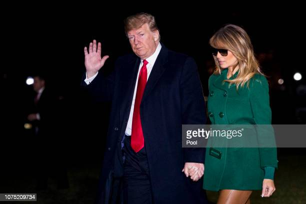 S President Donald Trump and First Lady Melania Trump make their way across the South Lawn of the White House after returning on Marine One from...