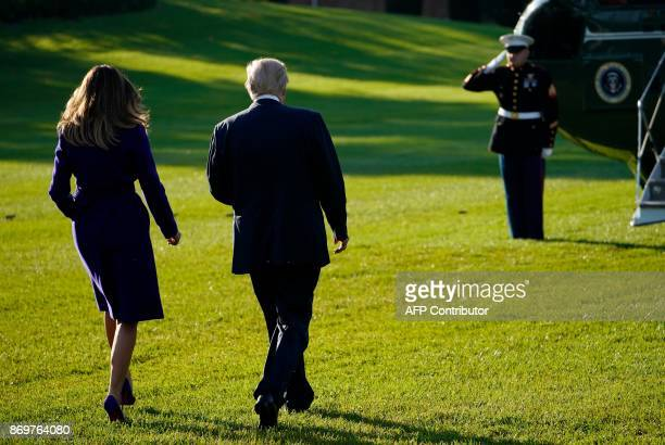 US President Donald Trump and First Lady Melania Trump make their way to board Marine One before departing from the South Lawn of the White House on...