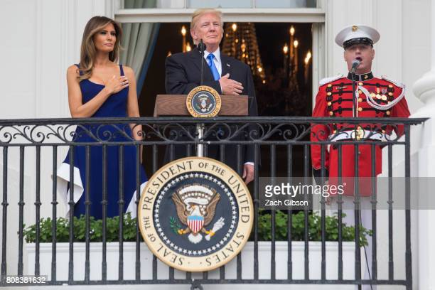 S President Donald Trump and first lady Melania Trump observe the playing of the national anthem from the Truman Balcony on July 4 2017 in Washington...