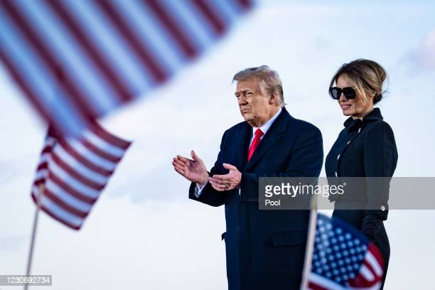 President Donald Trump and First Lady Melania Trump on stage after speaking to supporters at Joint Base Andrews before boarding Air Force One for his...