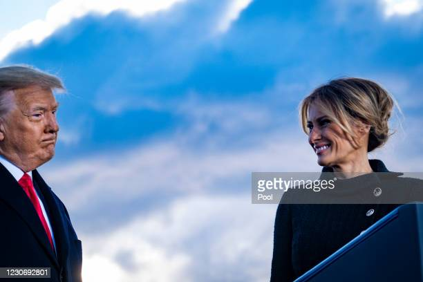 President Donald Trump and First Lady Melania Trump pause while speaking to supporters at Joint Base Andrews before boarding Air Force One for his...