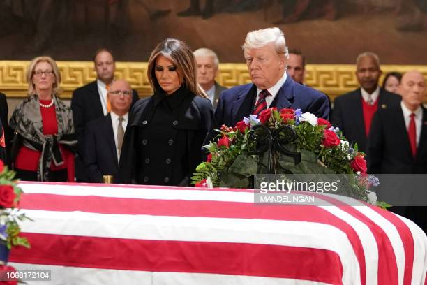 US President Donald Trump and First Lady Melania Trump pay their respects as US president George H W Bush lies in state in the Rotunda of the US...