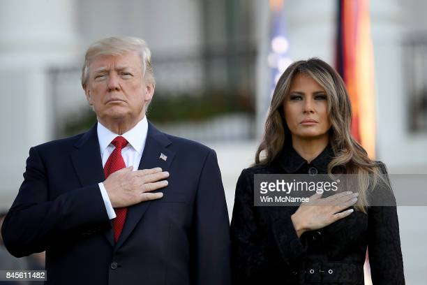 S President Donald Trump and first lady Melania Trump place their hands over their hearts on the South Lawn of the White House during the playing of...
