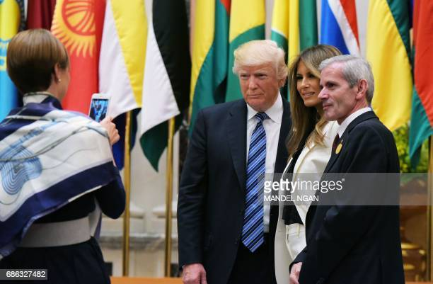 US President Donald Trump and First Lady Melania Trump pose for a photo with an unidentified man after taking part in the group photo during the Arab...