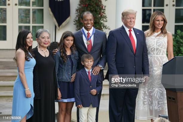 S President Donald Trump and First Lady Melania Trump pose for photos with professional golfer and business partner Tiger Woods and his family after...