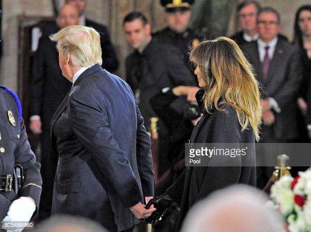 President Donald Trump and first lady Melania Trump return to their seats after laying a wreath during the ceremonies as the late evangelist Billy...