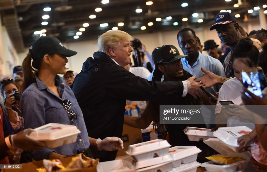US President Donald Trump and First Lady Melania Trump serve food to Hurricane Harvey victims at NRG Center in Houston on September 2, 2017. / AFP PHOTO / Nicholas Kamm