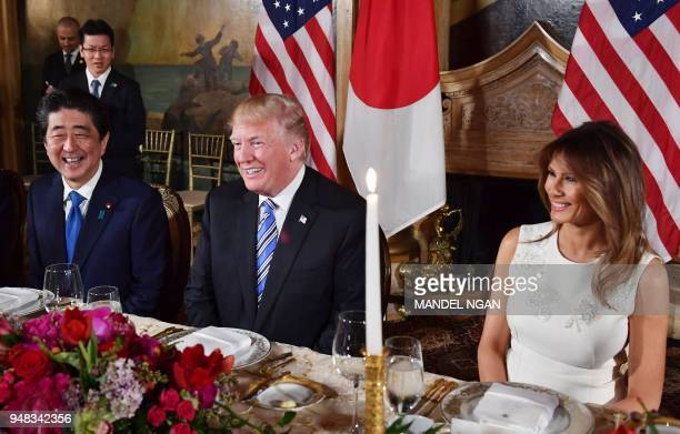 US President Donald Trump and First Lady Melania Trump smile during a dinner with Japan's Prime Minister Shinzo Abe at Trump's MaraLago estate in...
