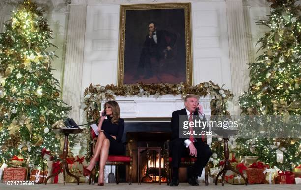 President Donald Trump and First Lady Melania Trump speak on the telephone as they answers calls from people calling into the NORAD Santa tracker...