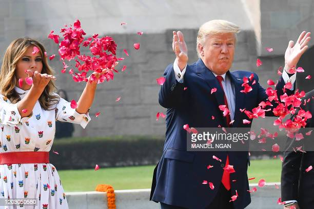 US President Donald Trump and First Lady Melania Trump spray rose petals to pay tribute at Raj Ghat the memorial for Indian independence icon Mahatma...