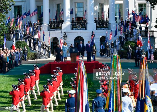 US President Donald Trump and First Lady Melania Trump stand at attention with Australian Prime Minister Scott Morrison and his wife Jenny Morrison...
