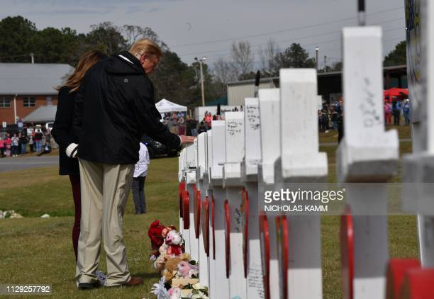 US President Donald Trump and First Lady Melania Trump stand before a row of crosses honoring 23 people who died in the storm outside Providence...