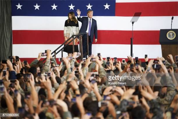 US President Donald Trump and first lady Melania Trump stand before a crowd at US Yokota Air Base in the suburbs of Tokyo on Nov 5 after arriving in...