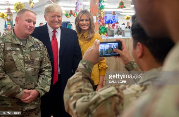 US President Donald Trump and First Lady Melania Trump take photos with members of the US military during an unannounced trip to Al Asad Air Base in...