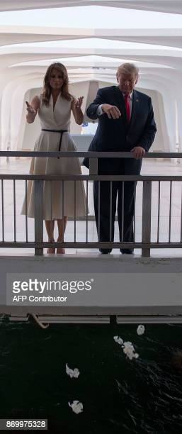 US President Donald Trump and First Lady Melania Trump throw flowers during their visit to the USS Arizona Memorial on November 3 at Pearl Harbor in...