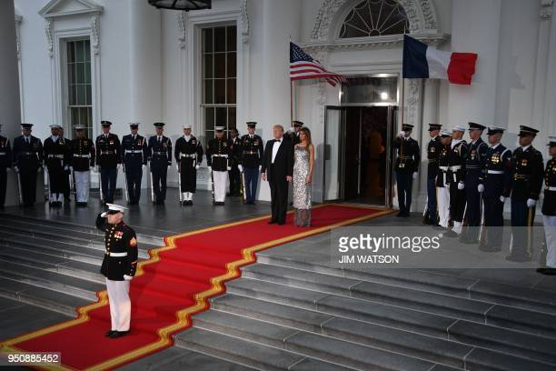 US President Donald Trump and First Lady Melania Trump wait for French President Emmanuel Macron and his wife Brigitte before a State Dinner at the...