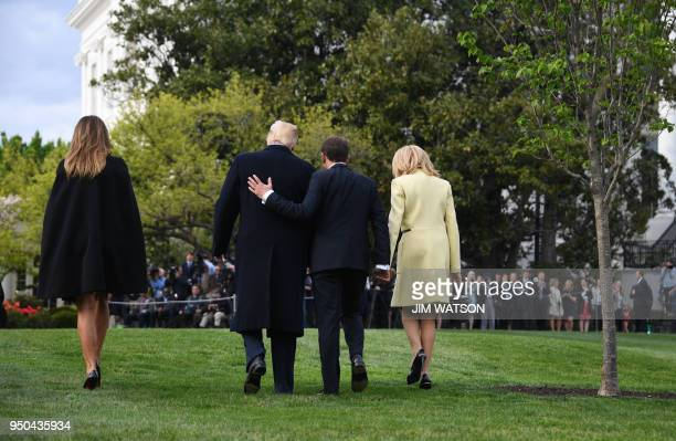 President Donald Trump and First Lady Melania Trump walk after a tree planting ceremony with French President Emmanuel Macron and his wife Brigitte...