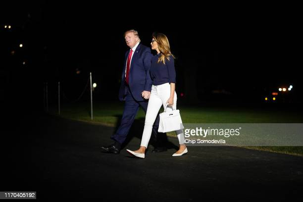 S President Donald Trump and first lady Melania Trump walk from Marine One to the White House after returning from the G7 summit August 26 2019 in...