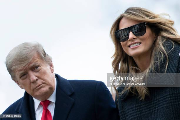 President Donald Trump and First Lady Melania Trump walk from Marine One as they return to the White House on December 31 in Washington, DC.