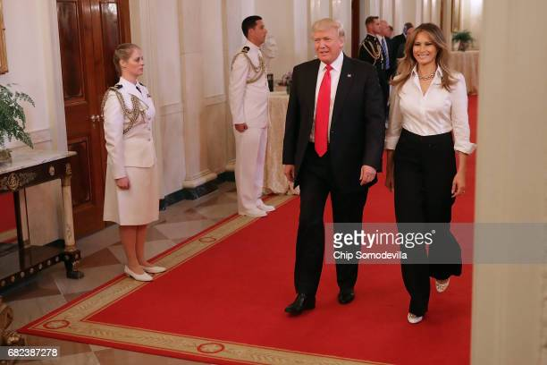 S President Donald Trump and first lady Melania Trump walk into the East Room for an event for military mothers on National Military Spouse...