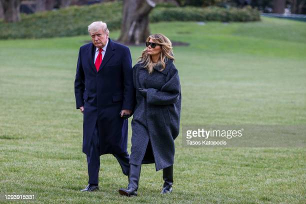 President Donald Trump and First Lady Melania Trump walk on the South Lawn while returning to the White House on December 31, 2020 in Washington, DC....