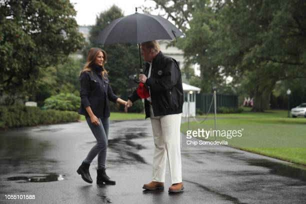 S President Donald Trump and first lady Melania Trump walk out of the White House before boarding Marine One and departing October 15 2018 in...